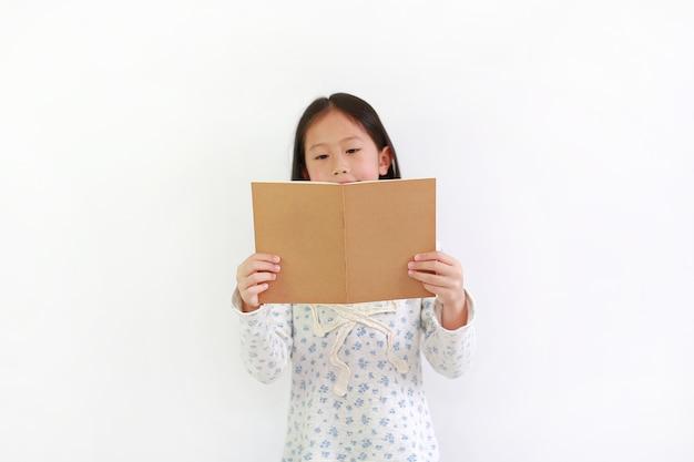Азиатский ребенок маленькой девочки держа коричневую книгу и читая над белой предпосылкой.