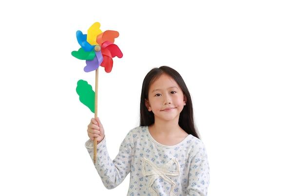 白い背景に分離されたカラフルな風車を保持しているアジアの小さな女の子の子供