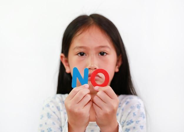 Азиатский ребенок маленькой девочки, не держащий текст губки в руках на белом фоне. концепция образования и развития. сосредоточьтесь на письмах в руке