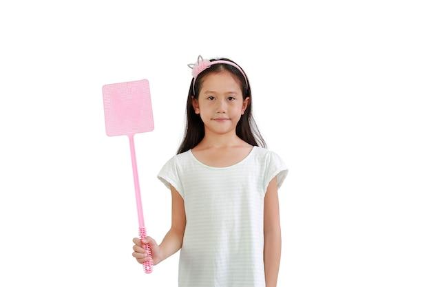 흰색 배경에 격리된 파리를 공격하기 위해 분홍색 파리채를 들고 있는 아시아 어린 소녀입니다. 클리핑 패스가 있는 이미지
