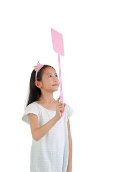 흰색 배경에 격리된 파리를 공격하기 위해 분홍색 파리채를 들고 있는 아시아 어린 소녀