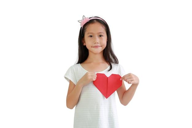 Asian little girl child holding red heart sign on chest against white background