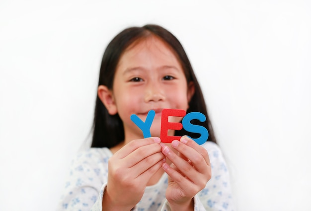 Азиатская маленькая девочка, держащая текст губки да в руках на белом фоне. концепция образования и развития. сосредоточьтесь на письмах в руке