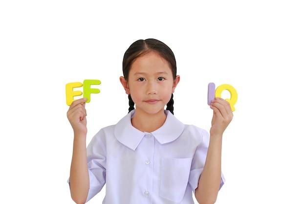흰색 배경에 고립 된 알파벳 ef 및 iq (실행 기능 및 지능 지수)를 들고 학교 유니폼 아시아 어린 여자 아이. 교육 개념. 클리핑 패스가있는 이미지