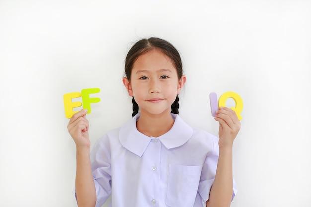 흰색 배경에 격리된 알파벳 ef와 iq(실행 기능 및 지능 지수)를 들고 교복을 입은 아시아 소녀. 교육 개념
