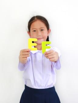 흰색에 알파벳 ef(집행 기능)를 들고 교복을 입은 아시아 소녀