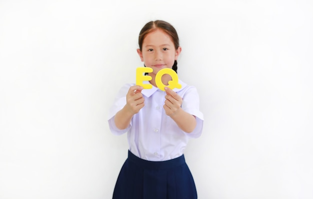 흰색 배경 위에 그녀의 얼굴에 알파벳 eq(감성 지수) 텍스트를 들고 교복을 입은 아시아 어린 소녀. 교육 개념입니다. 손에 있는 텍스트에 초점