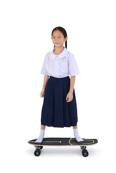 흰색 배경에 격리된 스케이트보드 위에 서 있는 태국 교복을 입은 아시아 어린 소녀입니다. 클리핑 패스가 있는 이미지 전체 길이