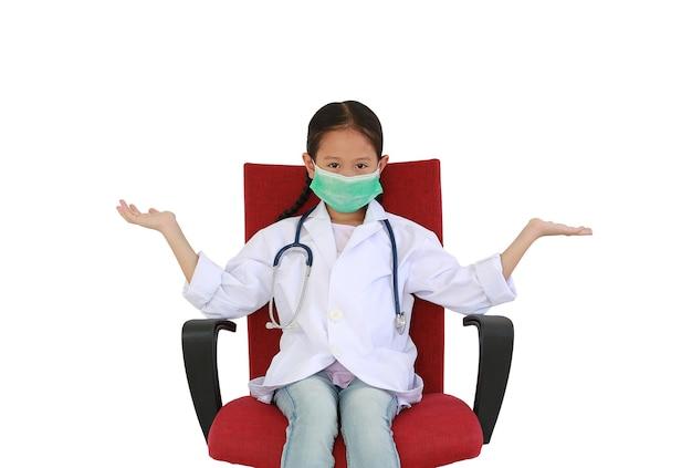 하얀색 의사 가운과 보호용 마스크를 쓴 아시아계 어린 소녀는 흰색 스튜디오 배경에 격리된 빨간 의자에 팔을 벌리고 앉아 있습니다. 클리핑 패스가 있는 이미지