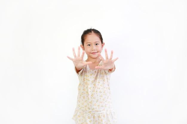 白い背景の上にジェスチャーを押すアジアの小さな女の子の子供彼の顔に選択的な焦点