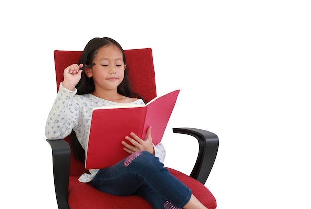 Азиатское усаживание книги чтения ребенка маленькой девочки и ослабляет на красном стуле ткани изолированном над белой предпосылкой. изображение с обтравочным контуром и копией пространства