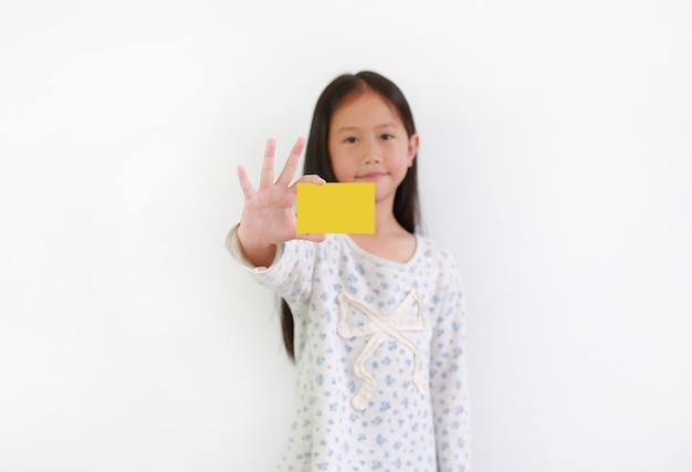 Азиатский ребенок маленькой девочки показывая пустую желтую карточку над белой предпосылкой. сосредоточьтесь на карте в руке