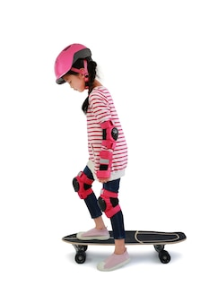 흰색 배경 위에 절연 스케이트보드에 스케이트 아시아 어린 소녀 아이. 스케이트보드를 타는 아이.