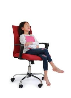 Азиатский ребенок маленькой девочки спит с обнимать книгу сидя на стуле красной ткани изолированном над белой предпосылкой. изображение в студии с обтравочным контуром