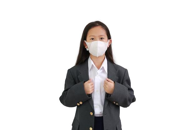 아시아계 어린 소녀는 정장 셔츠, 학생복, 보호용 안면 마스크를 착용하고 흰색 배경 위에 격리된 포즈로 양복을 들고 손을 유지합니다.