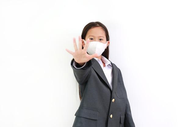 흰색 바탕에 손 정지 신호를 보여주는 정장 셔츠, 학생복, 보호용 얼굴 마스크를 쓴 아시아 소녀