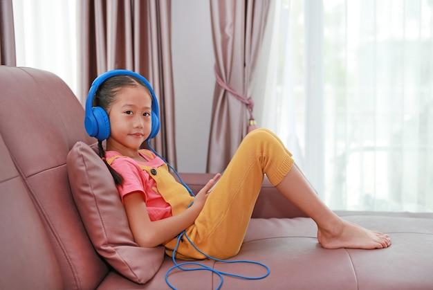 ヘッドフォンを着用し、家のリビングルームでソファに座ってスマートフォンを再生するアジアの小さな女の子の子供