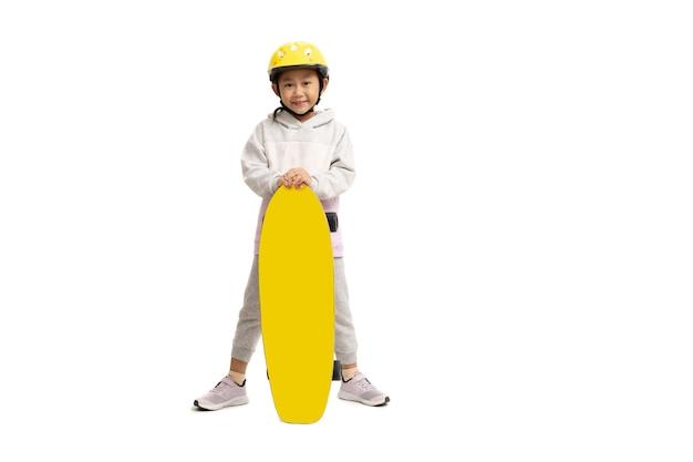 スケートボード、白い背景で隔離のアジアの小さな女の子の子供。