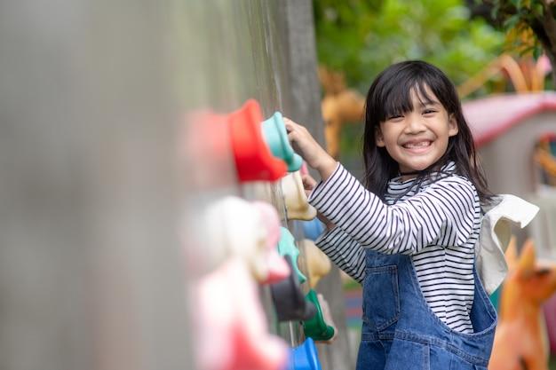 Азиатская маленькая девочка, восхождение на каменную стену