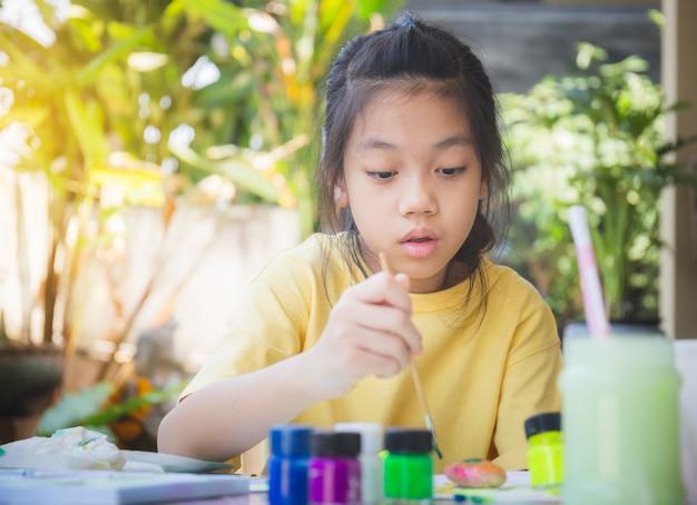 Азиатская маленькая девочка раскраски камни, дети творчества рок-мастера, детские концепции творчества Premium Фотографии