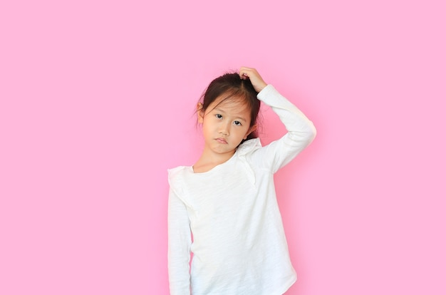 アジアの少女は混乱し、頭を引っ掻くジェスチャーを作ると不思議に思う