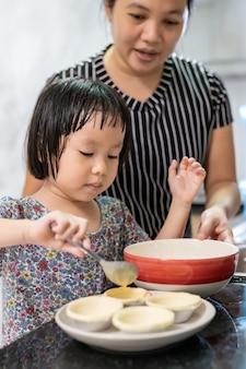 그녀의 엄마와 함께 요리하는 아시아 소녀