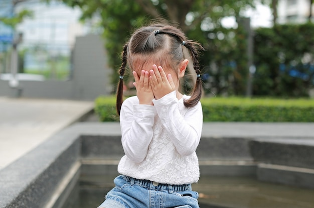 Asian little girl cover her face with her hands