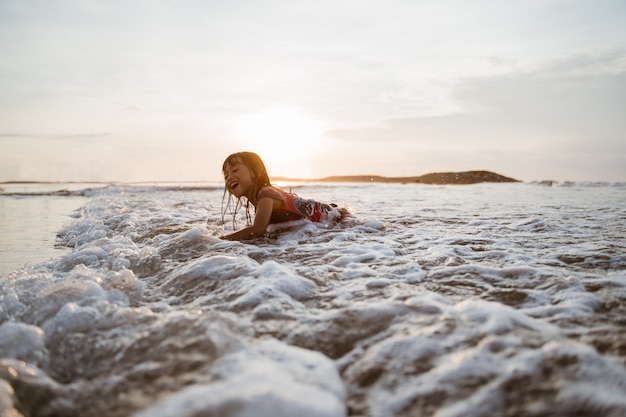アジアの女の子が水で遊んでいる間、ビーチの砂の上をクロールします。