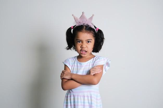 Азиатская маленькая девочка скрестила руки и показала сердитое выражение лица