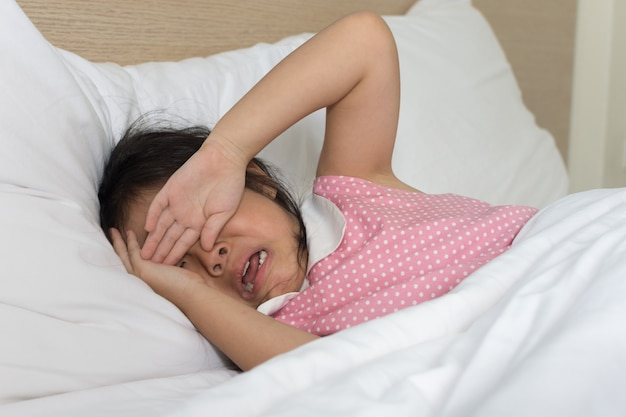 Asian little girl crying on bed