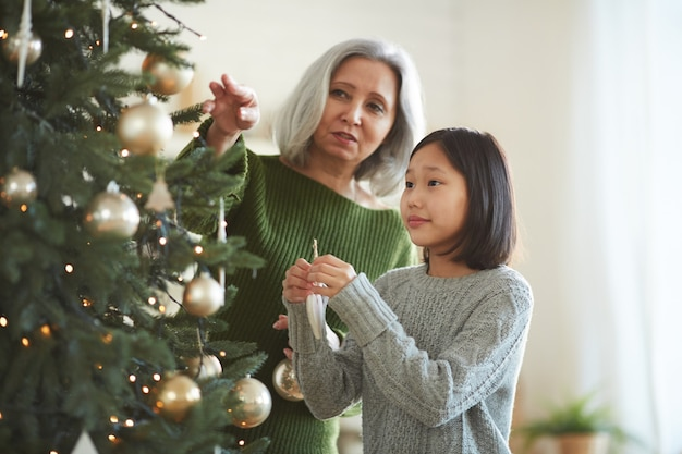 Asian little girl decorating christmas tree together with her mother at home