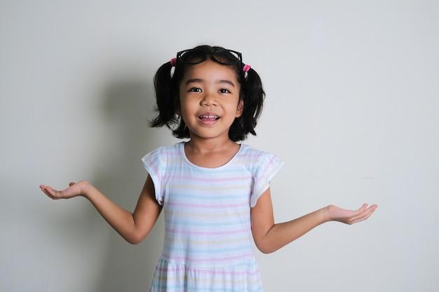 양손 손바닥이 위로 향하게 하여 혼란스러운 포즈를 취하고 있는 아시아 소녀