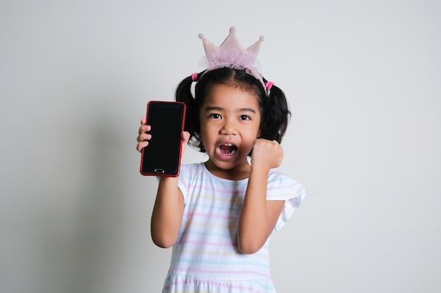 Asian little girl doing excited expression while showing blank mobile phone screen