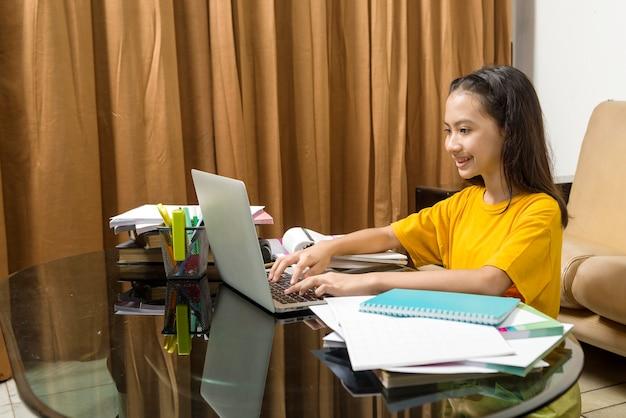 Азиатская маленькая девочка делает домашнее задание с ноутбуком дома. онлайн-обучение во время карантина