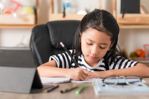 Asian little girl doing homework on wooden table select focus shallow depth of field