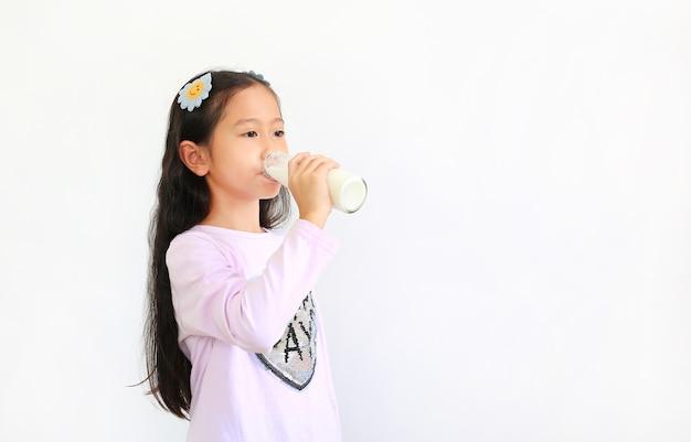 Asian little girl drinking milk from glass bottle isolated