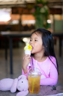 Азиатская маленькая девочка ест мороженое с напитком и куклой в помещении