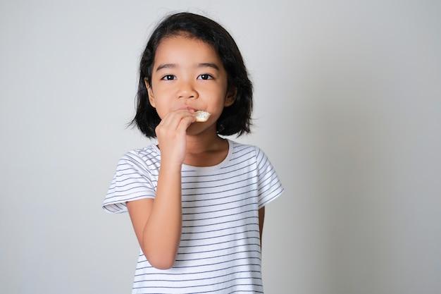 Азиатская маленькая девочка ест печенье, изолированные на белом фоне