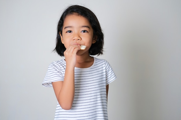 Asian little girl eating biscuit isolated on white background