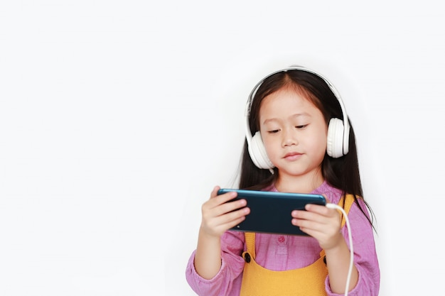 Asian little girl enjoys listening music with headphones