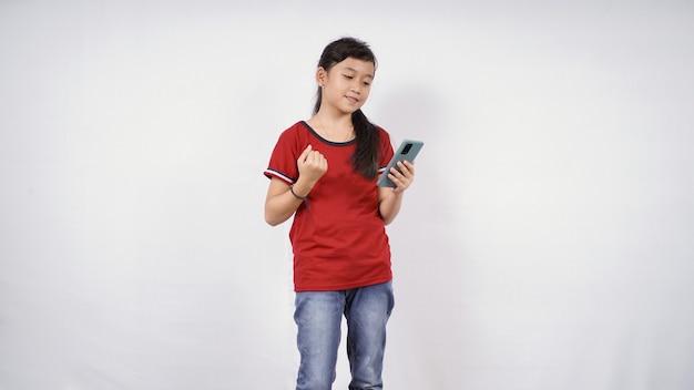 白い背景で隔離の彼女のスマートフォンゲームで成功を感じているアジアの少女