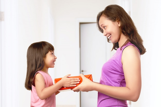 Asian little girl giving her mother a gift box