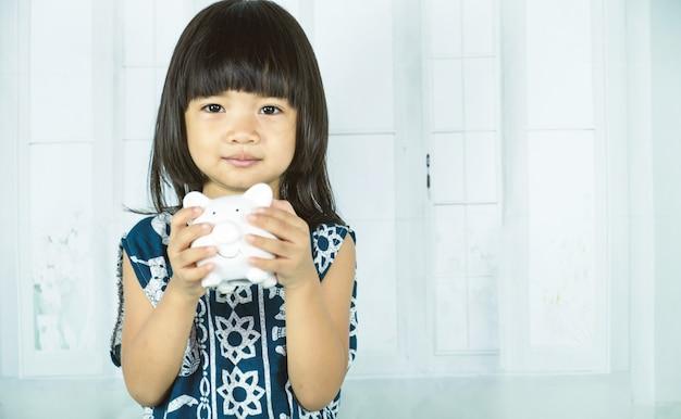 아시아 어린 소녀가 흰 돼지 저금통을 들고 미래의 개념을 위해 저축하는 법을 배웁니다.