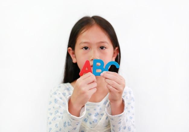 흰색 배경 위에 abc 스폰지 텍스트를 손에 들고 아시아 어린 소녀. 손에 든 글자에 집중