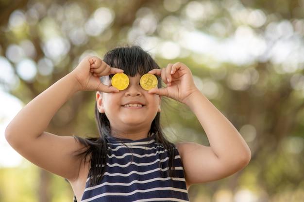 Азиатская маленькая девочка держит биткойн цифровые деньги. концепция легкого инвестирования и торговли биткойнами.