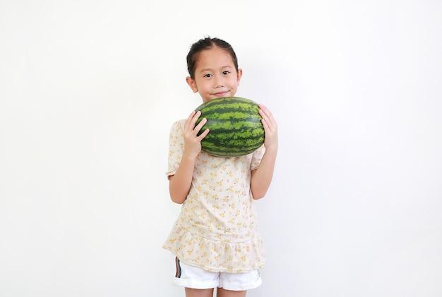 Asian little girl holding fresh green watermelon on white