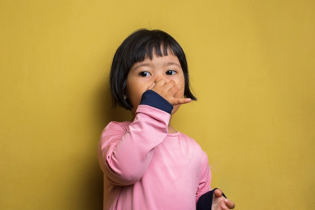 Asian little girl holding her nose because of a bad smell