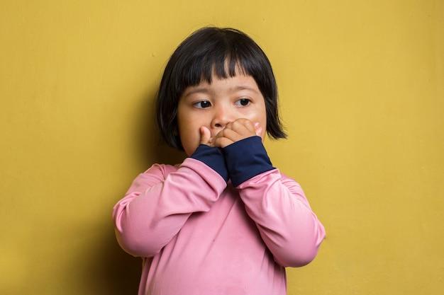 悪臭のために鼻を抱えているアジアの少女