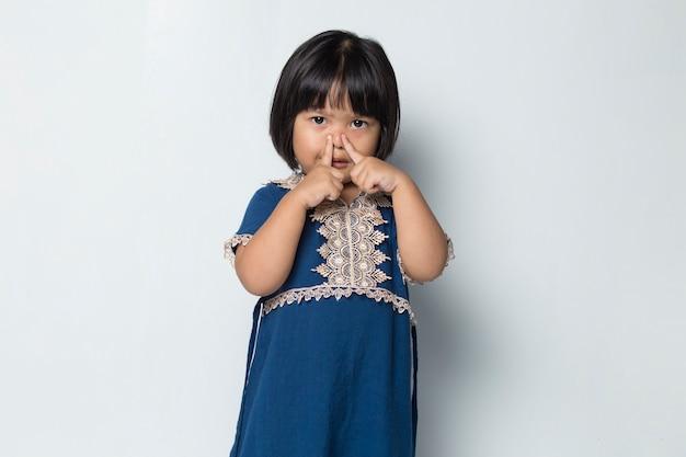 나쁜 냄새 때문에 코를 잡고 있는 아시아 소녀