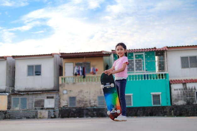 Asian little girl holding skateboard and smile with happiness town and blue sky select focus shallow depth of field